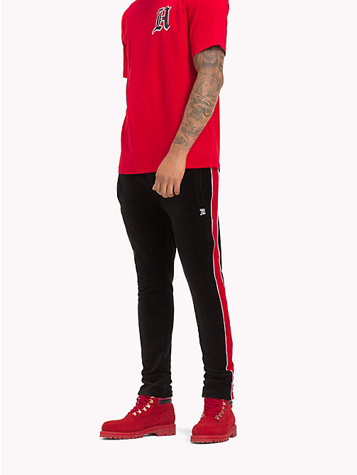TOMMY HILFIGER Striped Velvet Tracksuit Bottoms - JET BLACK / BARBADOS CHERRY - TOMMY HILFIGER TOMMY NOW MEN - main image